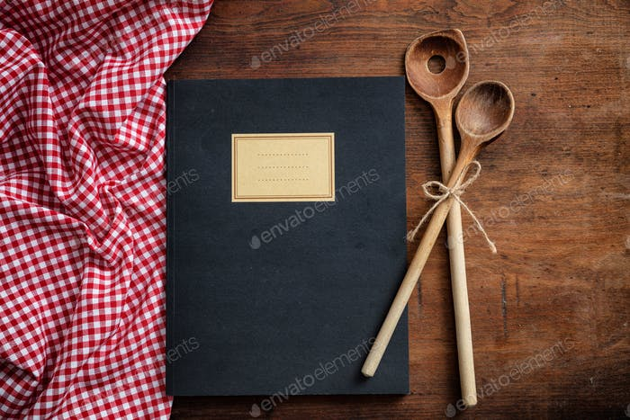 Notebook, kitchen utensils and red tablecloth on wooden table, top view