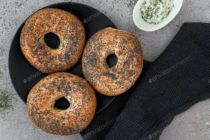 Bagels auf einem schwarzen Teller angeordnet auf einer Marmortheke