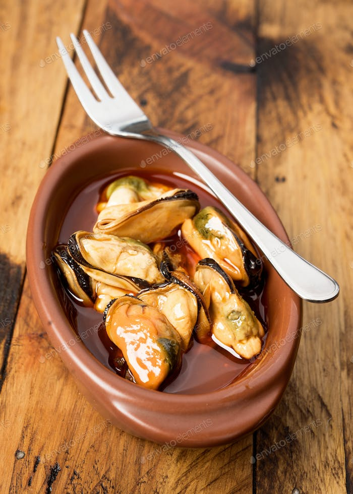clay bowl with mussels in sauce, on dark wooden board