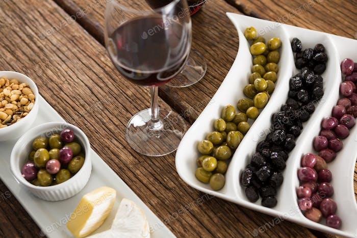 Nahaufnahme von marinierten Oliven mit Gläsern Wein