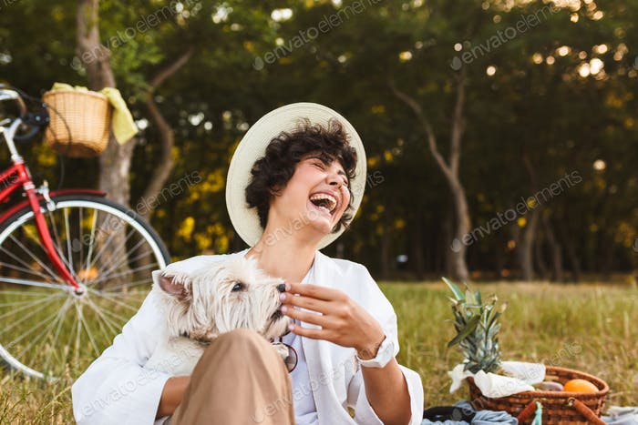 Nice laughing girl in hat holding little dog in hands happily sp