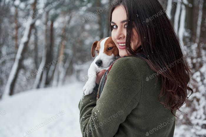 Cheerful mood. Smiling brunette having fun while walking with her dog in the winter park