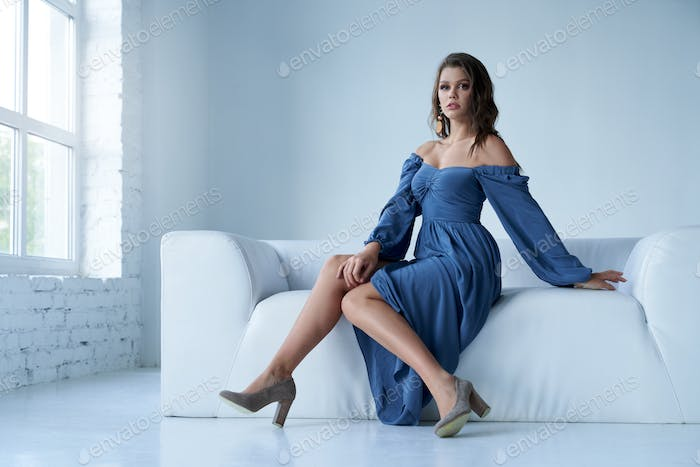 Stylish female model in midi dress on couch