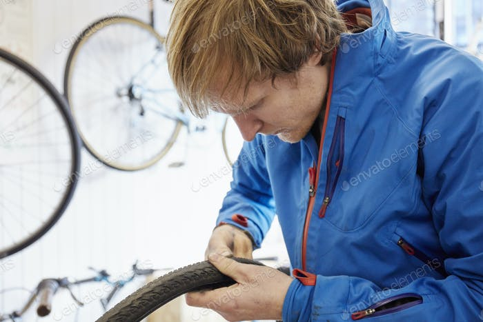A young man working in a cycle shop, repairing a bicycle.