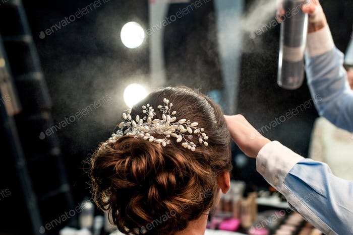 cropped shot of hairstylist fixating clients hairdo with hair spray