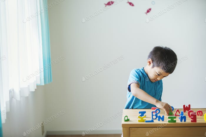 A boy playing with colourful alphabet letters.