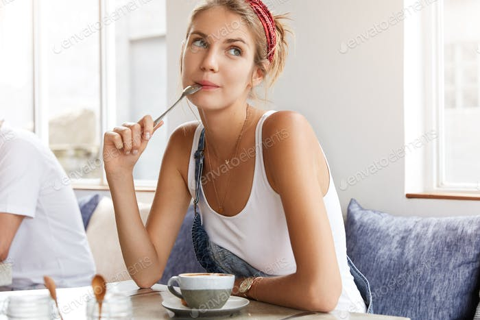 Dreamy beautiful carefree woman has coffee break after working day, dreams about weekends or day off