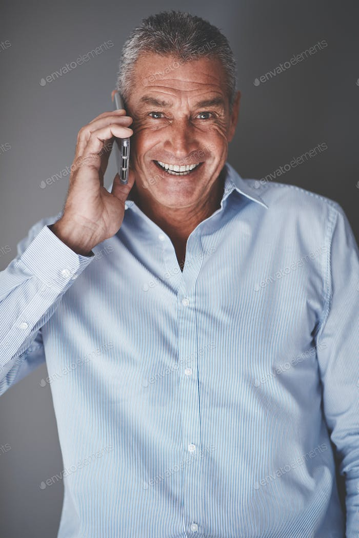 Smiling mature businessman using his cellphone against a gray background