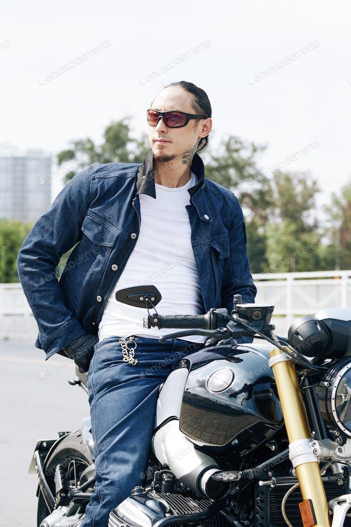 Hombre guapo sentado en la motocicleta