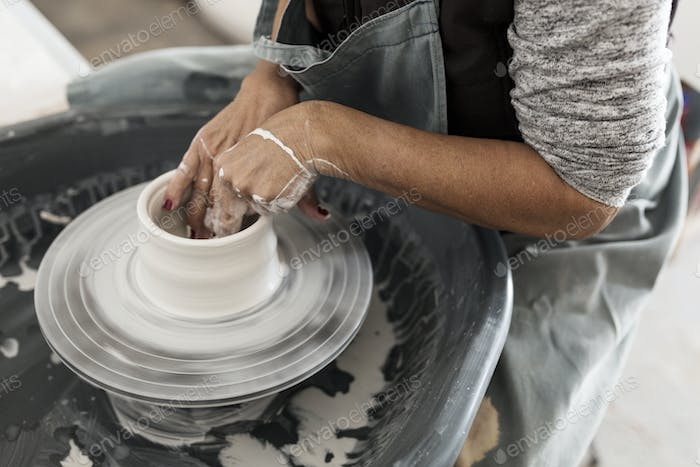 Mid section of woman making pottery
