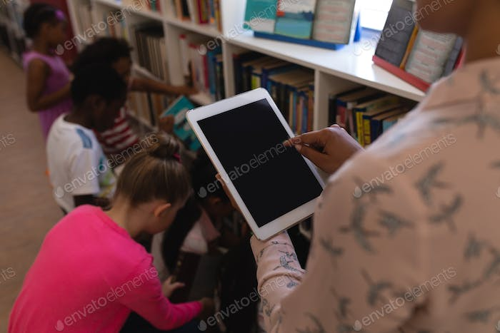 Rear view of female teacher working on digital tablet with schoolkids behind her in school library