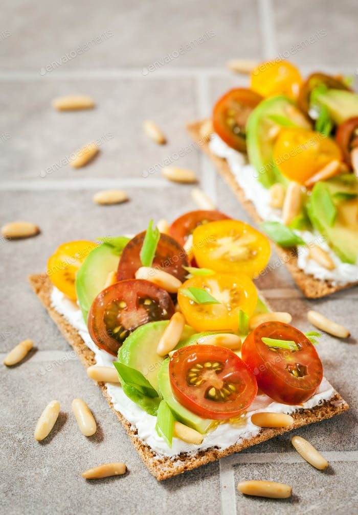 Сrisp bread toast  with cream cheese, fresh avocado, cherry tom