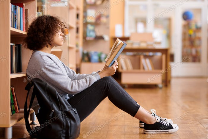 Mixed-race girl in casualwear reading book in college library