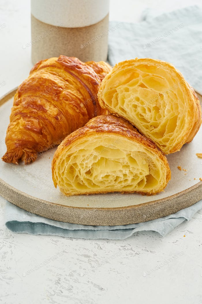 Two delicious croissants on plate and hot drink in mug. Croissant sectional view,
