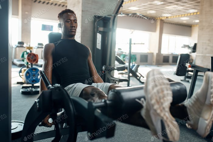 Muscular athlete in sportswear at exercise machine