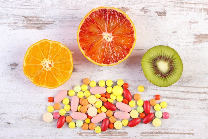 Fresh fruits and colorful medical pills, choice between healthy nutrition and medical supplements