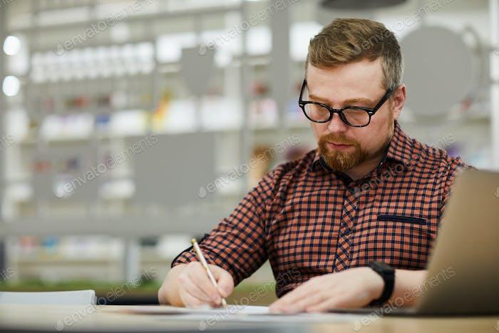 Thoughtful man preparing report