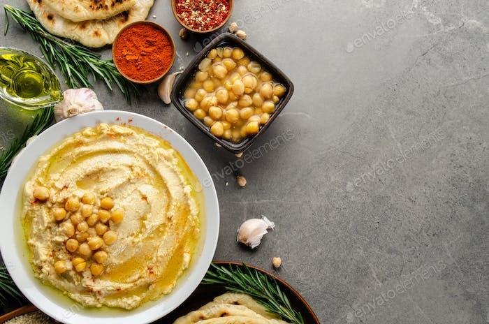Hummus gekrönt mit Kichererbsen, Olivenöl und grünen Korianderblättern auf Steintisch