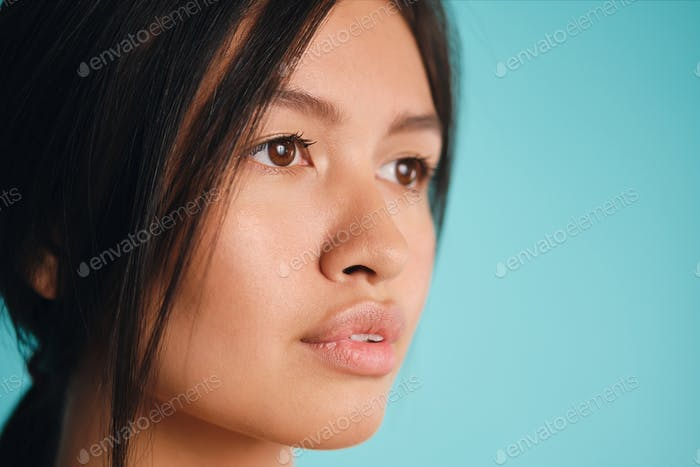 Close up beautiful Asian brunette girl dreamily looking away over colorful background
