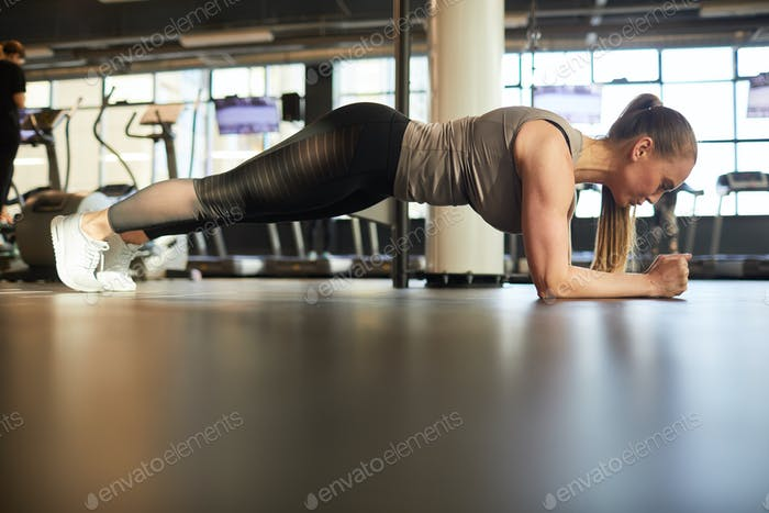 Young Woman Doing Plank Exercise in Gym Side View