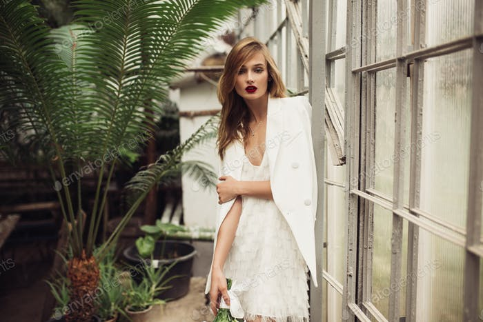 Young beautiful woman in white jacket and dress thoughtfully loo