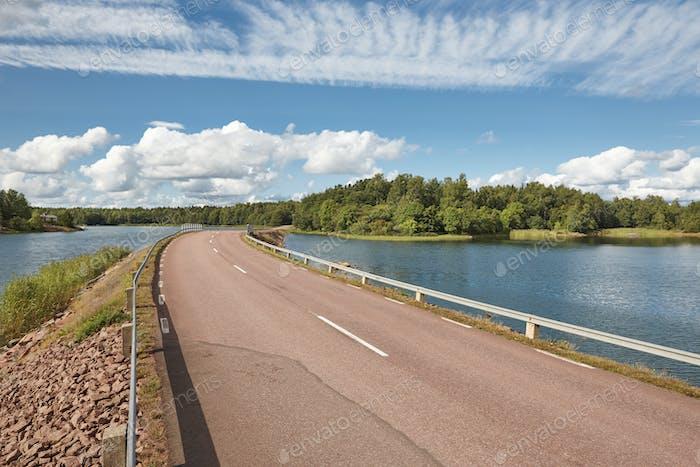 Finnische Landschaft mit Straße, See und Waldinsel. Finnland. Europa