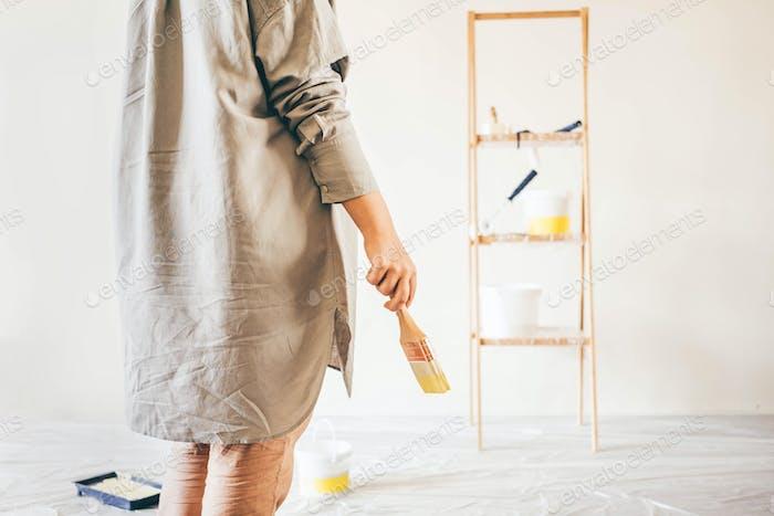 женщина с краской росписью стены.