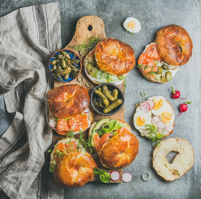 Variety of bagels with different fillings on rustic wooden board