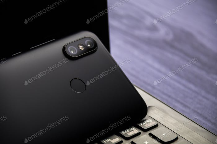 Moderner Notebook- und Smartphone-Kopierraum. Mobil mit Dual-Kamera und Fingerabdruckleser