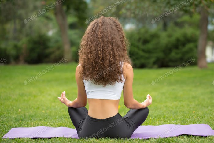 Pretty woman sitting back doing yoga meditation