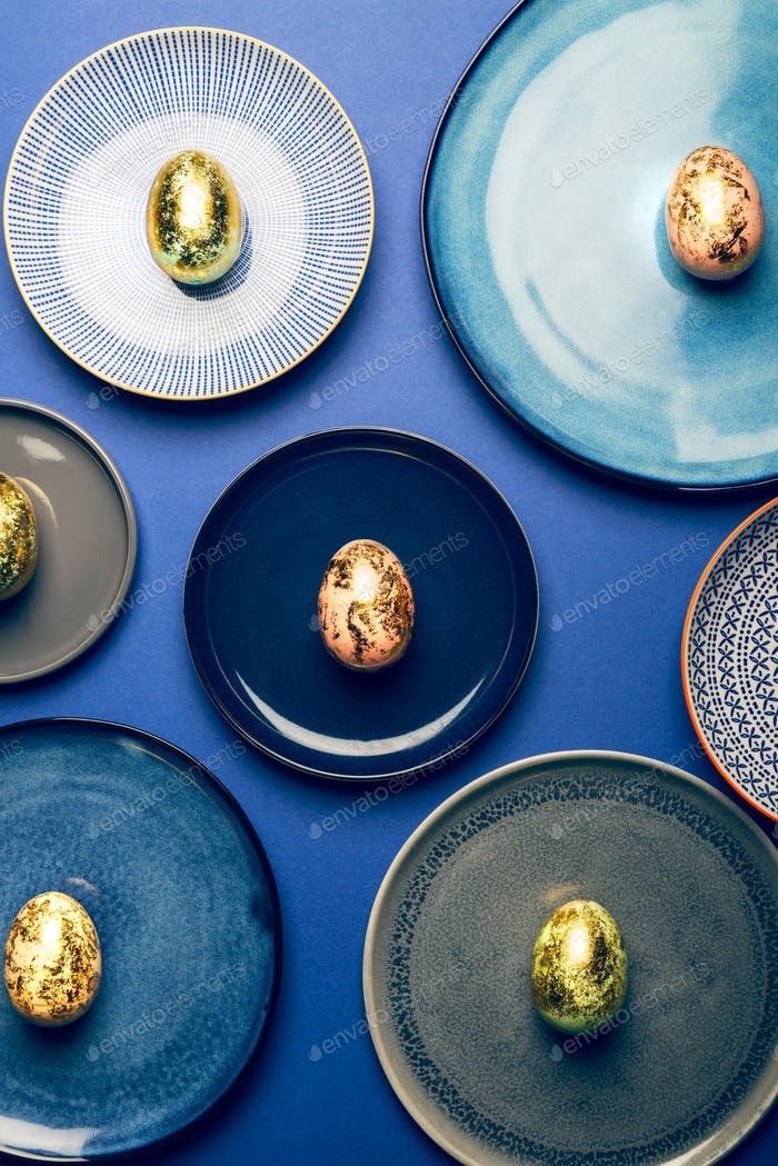Different Plates with Easter Eggs of pastel colors on blue background