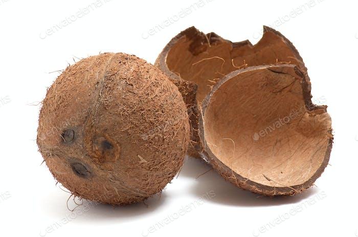 Ganze und gebrochene Kokosnuss auf weißem Hintergrund.