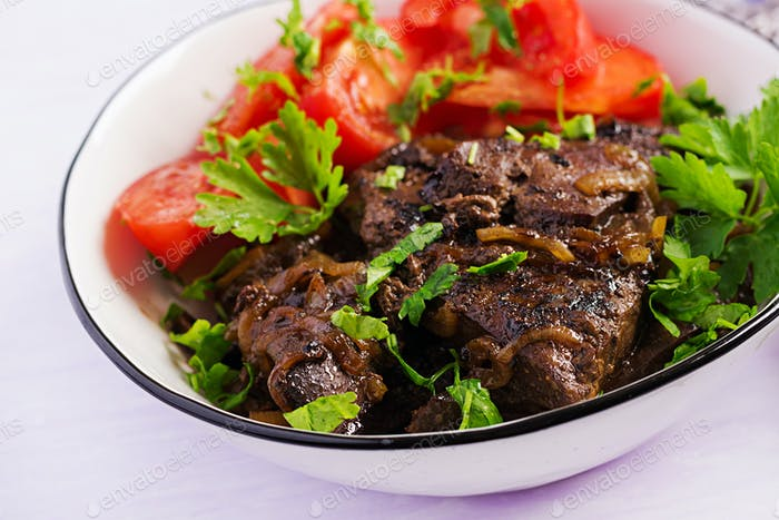 Roasted or grilled beef liver with onion and tomatoes salad. Middle Eastern cuisine.