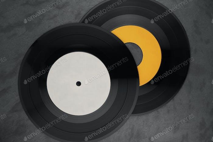 Two single vinyl records on black background.