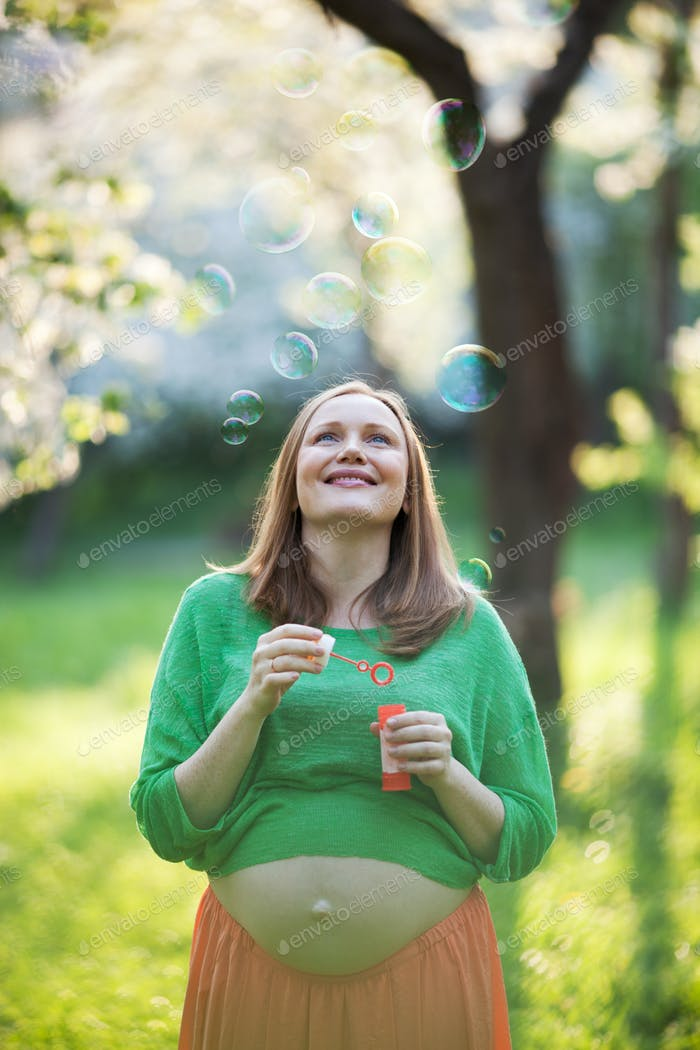 Happy pregnant woman and bubbles outdoor