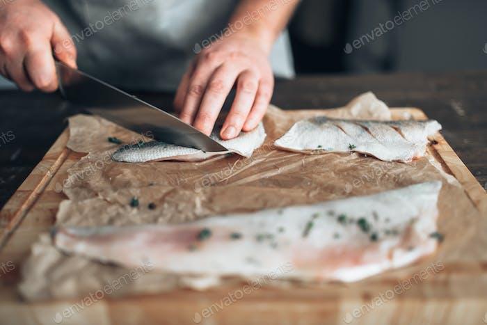 Chef schneidet rohe Fischscheiben auf Holzschneidebrett