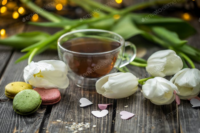 white tulips and a transparent Cup of tea