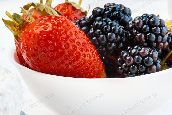 Fresh berries in glass pot.