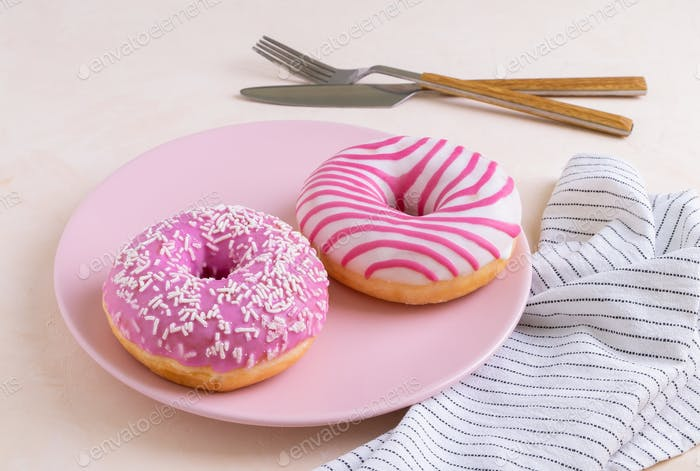 Two sugar-coated donuts lie on a pink ceramic plate. Serving with cutlery and linen napkin.
