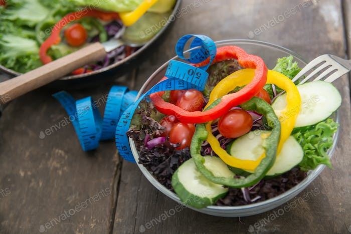 Fresh vegetables salad on  bowl with measuring tape over wooden background.