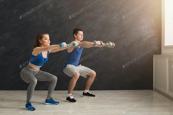 Junges Paar in Sportbekleidung tun hocken
