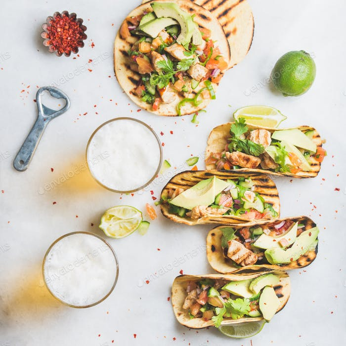 Healthy corn tortillas with chicken, avocado, salsa, limes and beer