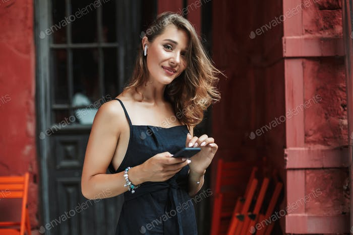 Young gorgeous woman in black dress with wireless earphones hold