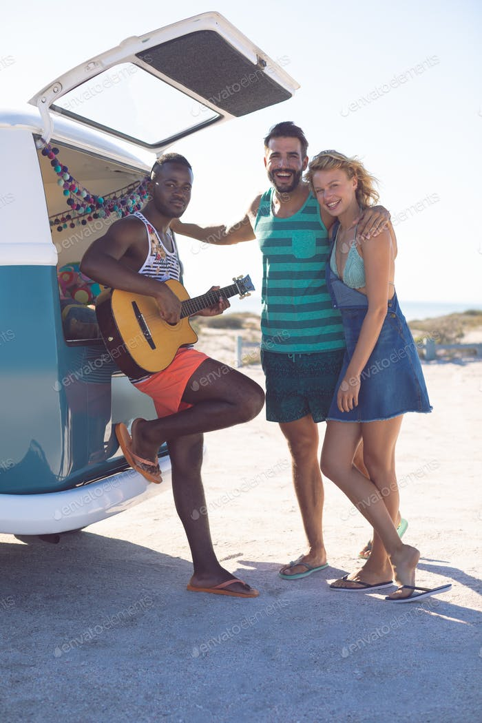 Front view of happy group of diverse friends having fun together near camper van at beach