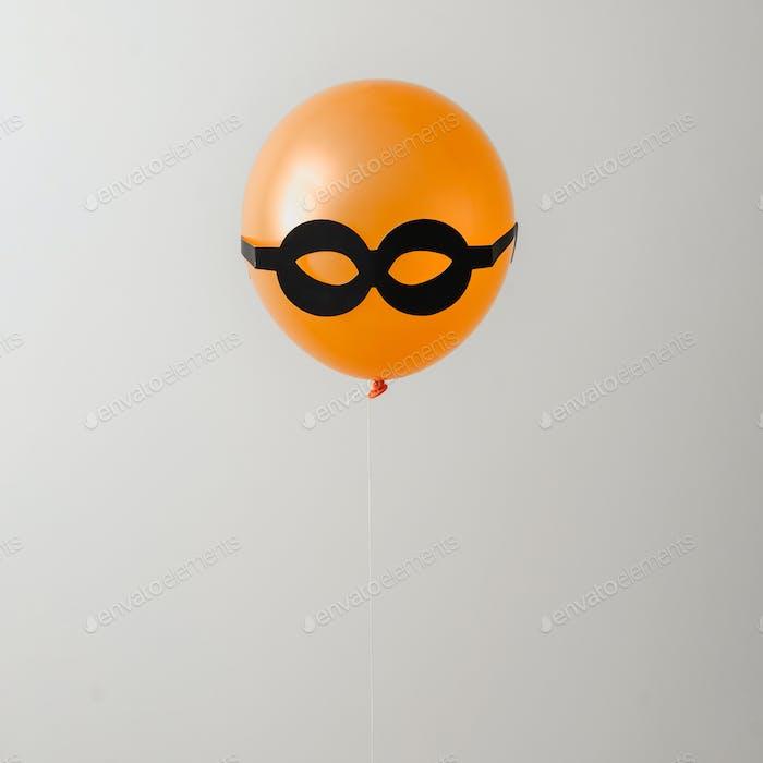 Balloon orange and black glasses. Party or hidden criminal concept. Minimal idea.