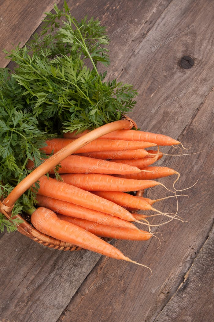 fresh carrots in wicker basket bunch on grungy wooden background