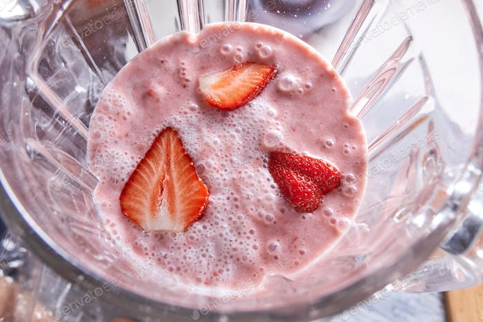 Freshly prepared strawberry smoothie in a blender bowl. Healthy food. Top view