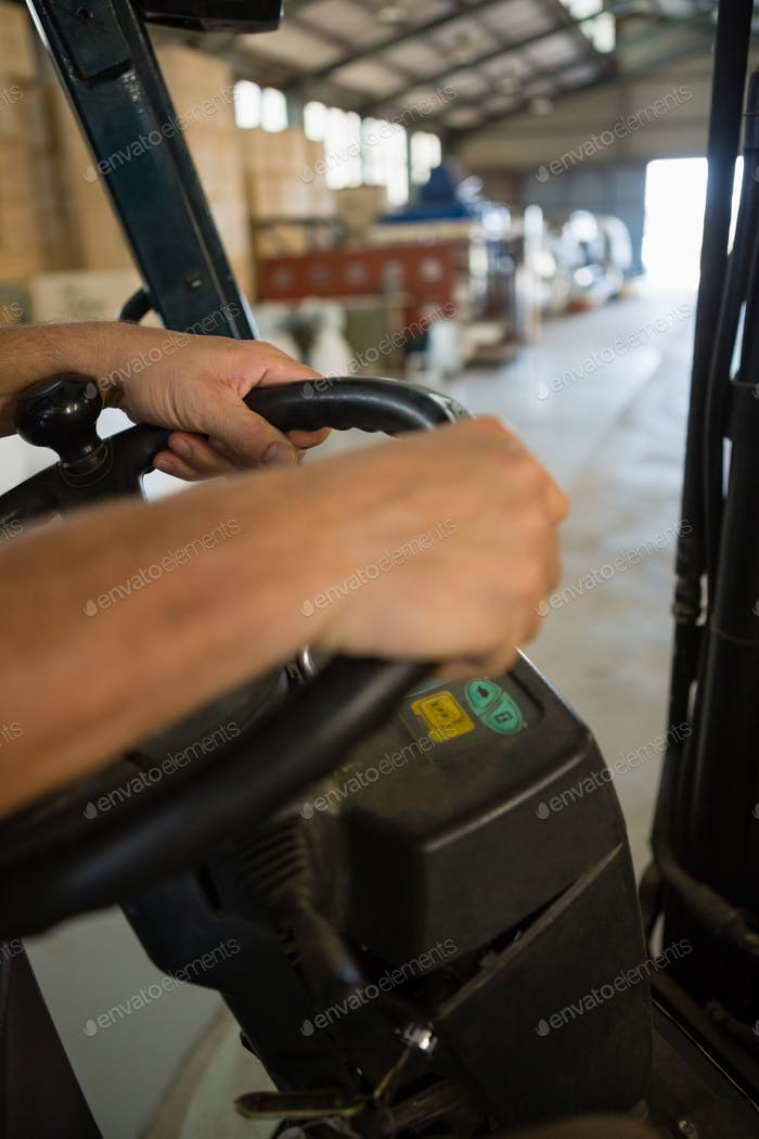 Mid-section of man driving a forklift car