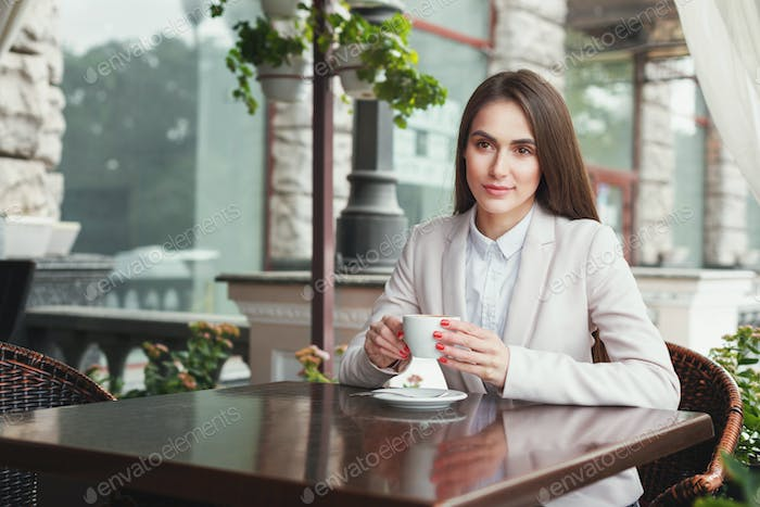 Young businesswoman outdoors drinking coffee