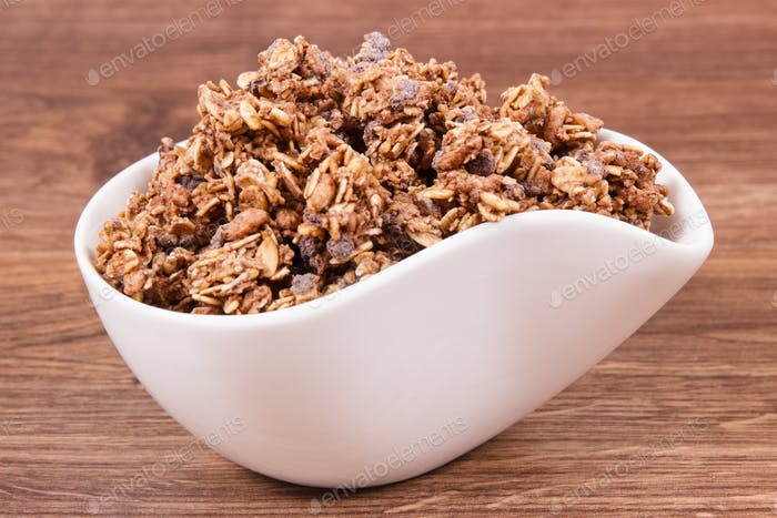 Oat flakes with chocolate in bowl, healthy food for breakfast concept